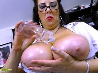 Mature secretary oils up her huge tits in the office