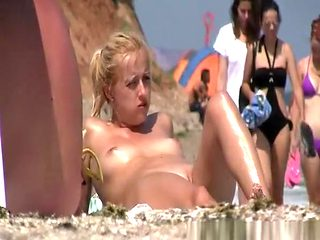 Nudist blonde with shaved pussy at beach