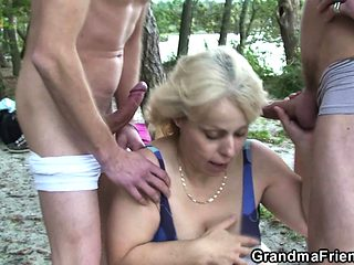 Very old granny takes two cocks from both sides outdoors