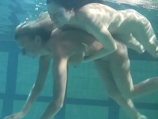 Two sexy lassie fool around in the nude while being submerged in water