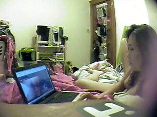 Asian girl watches porn and rubs pussy
