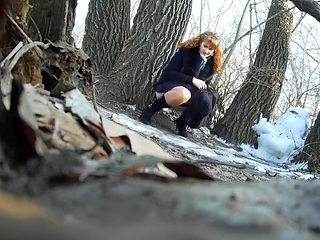 Ginger bridesmaid makes water behind a tree in the forest