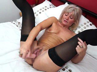 Granny pussy opens wide around a big dildo as she fucks solo